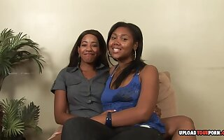 Two horny ebony ladies are having some fun lesbian time together with a strap-on toy